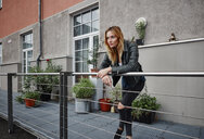 Confident young woman wearing biker jacket leaning on balcony railing - RHF02369