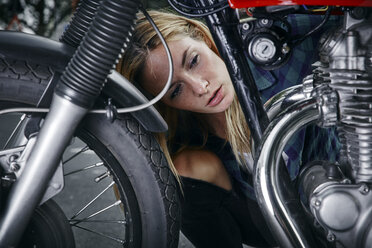 Young woman working on motorcycle - RHF02375