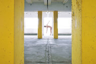 Full length of a nude man standing against a yellow wall in a building - INGF04164