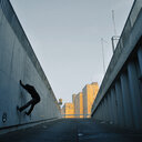 Full length of a man climbing onto a wall in Germany - INGF04230
