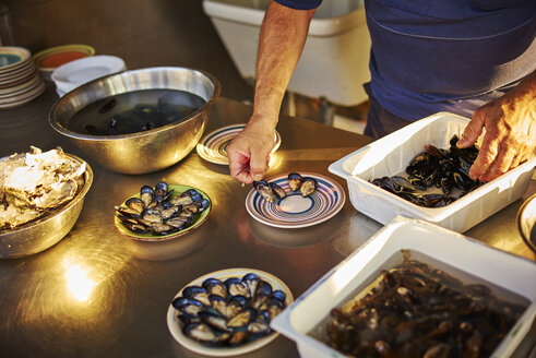 Man preparing and arranging fresh mussels - DIK00297