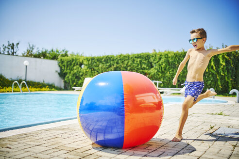 Boy at the poolside sunglasses kicking great beach ball - DIKF00300