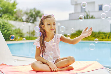 Girl playing with soap bubbles at the poolside - DIKF00303