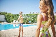 Boy with water gun splashing at girl at the poolside - DIKF00306