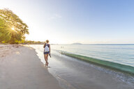 Seychelles, Mahe, Beau Vallon Beach, woman walking at the beach at sunset - MMAF00679