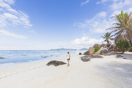 Seychelles, La Digue, Anse Source d'Argent, woman walking at the beach - MMAF00688