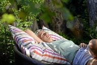 Woman relaxing on big cushion in the garden - BFRF01919