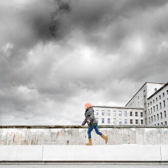 A young girl walking along a wall in Berlin under cloudy skies - INGF04384