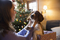 Teenage girl petting cute dog in Christmas gift box - HOXF03953