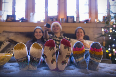Family with colorful socks relaxing, watching TV in living room - HOXF03968