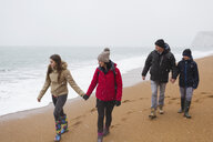 Family in warm clothing walking on snowy winter beach - HOXF03977