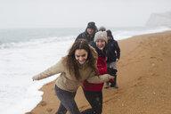 Happy, carefree family on snowy winter beach - HOXF03983