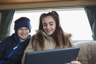 Teenage brother and sister using digital tablet in motor home - HOXF04013