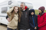 Portrait happy family in warm clothing outside motor home - HOXF04022