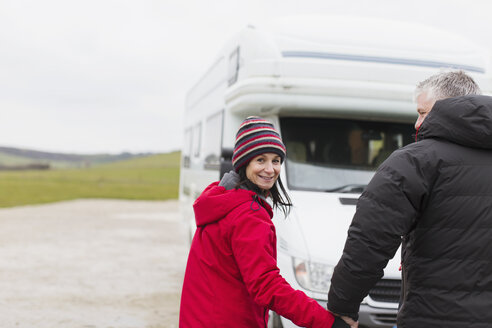 Portrait smiling couple in warm clothing holding hands outside motor home - HOXF04028