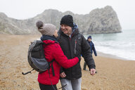 Affectionate, happy couple in warm clothing on snowy winter beach - HOXF04034
