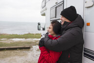 Affectionate couple in warm clothing hugging outside motor home - HOXF04037