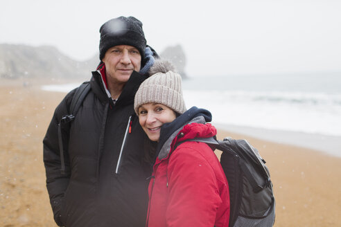 Portrait couple in warm clothing on winter beach - HOXF04040