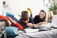 Laughing young women friends with laptop on bed - HOXF04082