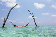 Woman laying in hammock over tranquil ocean, Maldives, Indian Ocean - HOXF04142