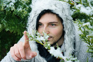 Portrait of young man touching snow covered branch outdoors - INGF05208