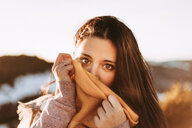 Girl covering herself with a scarf looking into the camera - INGF05217