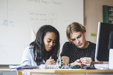 Confident female student preparing science project with young male friend on desk in classroom at high school - MASF09296