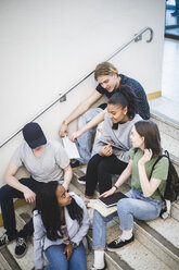 High angle view of multi-ethnic students talking and sitting on steps at high school - MASF09305