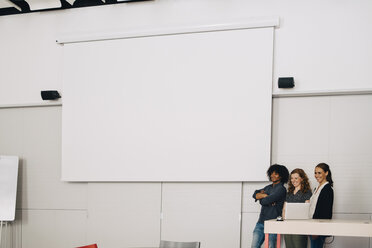 Smiling multi-ethnic technicians standing by blank projection screen at creative office - MASF09344