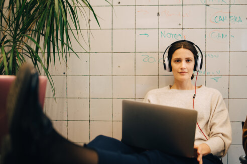 Portrait of confident young female computer hacker listening through headphones while sitting with laptop against tile w - MASF09386