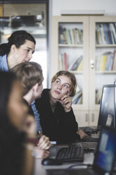 Confident female mature teacher discussing with male students while looking at computer monitor in classroom - MASF09452