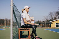 Side view of tired senior woman sitting on bench against sky at tennis court - MASF09482