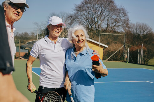 Happy senior friends looking away while holding tennis racket at court - MASF09485