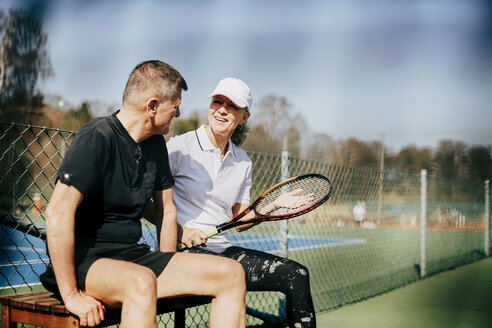 Smiling senior friends talking while sitting on bench at tennis court - MASF09488