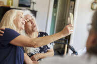 Happy senior friends taking selfie on mobile phone while vlogging at home - MASF09497