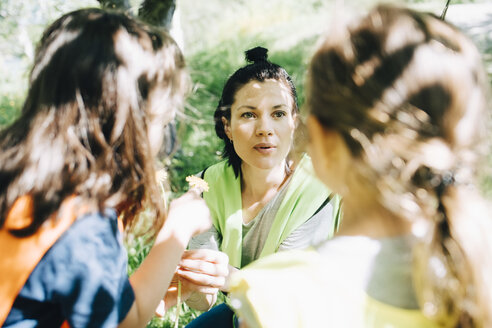 High angle view of teacher talking with girls in playground - MASF09521