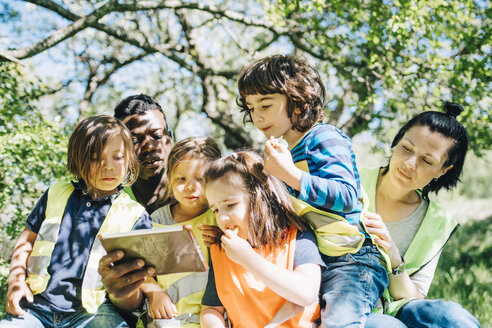 Multi-ethnic students and teachers sharing digital tablet while sitting against trees in playground - MASF09527