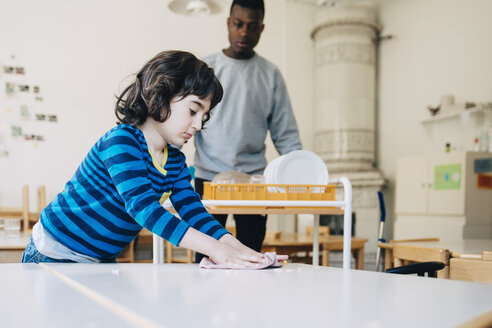 Boy cleaning table with dish cloth while teacher standing in classroom at kindergarten - MASF09551