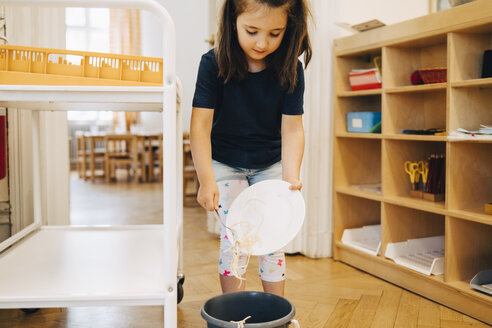 Girl throwing spaghetti in garbage can at kindergarten - MASF09554