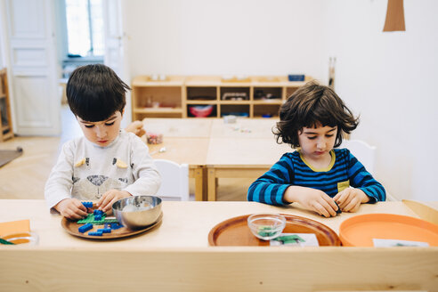 Male students playing with toys at table in child care classroom - MASF09581