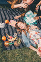 High angle view of young woman lying by friends enjoying picnic during summer at back yard - MASF09590