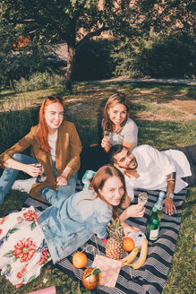 High angle portrait of young multi-ethnic friends enjoying picnic during summer at back yard - MASF09593