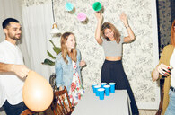 Young multi-ethnic friends enjoying beer pong game at apartment during dinner party - MASF09596