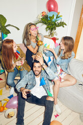 Portrait of smiling young man holding pineapple while sitting against female friends enjoying party at home - MASF09605