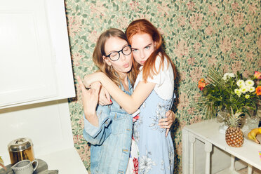 Portrait of young redhead woman embracing female friend showing horn sign at home - MASF09611