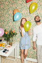 Young man and woman playing with balloons while standing against wallpaper at home during dinner party - MASF09617