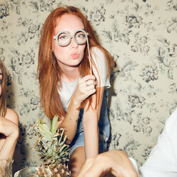 Portrait of young redhead woman holding eyeglasses prop while sitting amidst friends during dinner party at home - MASF09686