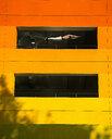 Shirtless man falling beside orange parking lot - LUXF02083
