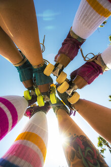 Low angle view of raised legs of women in roller skates - LUXF02086