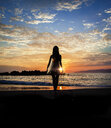 Silhouette of young woman with surfboard on beach at sunset - LUXF02095